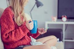 Moça doente com comprimidos e copo do chá que senta-se no sofá imagem de stock