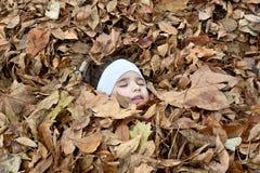 Moça e as folhas de outono Fotos de Stock Royalty Free