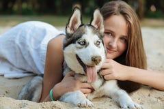 Moça e seu cão (roncos) que anda no outono em um parque da cidade Imagem de Stock