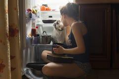 Moça e seu gato macio que comem na noite Fotografia de Stock Royalty Free