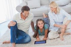 Moça e seus pais que usam uma tabuleta foto de stock