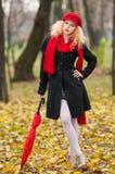 Moça elegante bonita com guarda-chuva vermelho, o tampão vermelho e o lenço vermelho no parque Imagem de Stock Royalty Free
