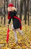 Moça elegante bonita com guarda-chuva vermelho, o tampão vermelho e o lenço vermelho no parque Foto de Stock