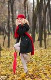 Moça elegante bonita com guarda-chuva vermelho, o tampão vermelho e o lenço vermelho no parque Imagens de Stock Royalty Free