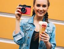 Moça elegante bonita que levanta em um revestimento do vestido e da sarja de Nimes do verão com a câmera cor-de-rosa do vintage e Imagens de Stock Royalty Free