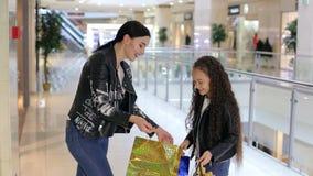 Moça elegante com a irmã mais nova que anda na alameda e na compra vídeos de arquivo