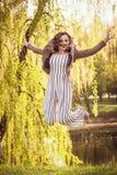Moça elegante que salta felizmente no fundo do parque foto de stock
