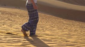 A moça em calças asiáticas anda ao longo da areia do deserto vermelho em Mui Ne, Vietname video estoque