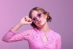 Moça em careta do amor e levantamento engraçado em um fundo cor-de-rosa com as estrelas dos vidros cor-de-rosa imagem de stock