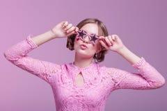 Moça em careta do amor e levantamento engraçado em um fundo cor-de-rosa com as estrelas dos vidros cor-de-rosa foto de stock