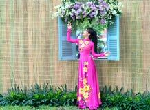 Moça em flores de observação da janela na camisa de vestido longa Foto de Stock