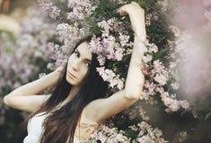 Moça em flores lilás Imagens de Stock Royalty Free