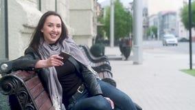 A moça em um casaco de cabedal preto e em um lenço cinzento senta-se em um banco e em olhares no telefone Levanta seus cabeça e r video estoque