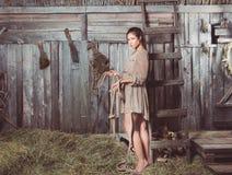 Moça em um celeiro com uma corda em suas mãos imagens de stock royalty free