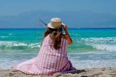 Moça em um chapéu de palha na praia que aprecia as vistas bonitas Imagens de Stock Royalty Free