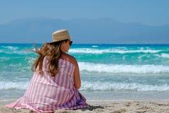 Moça em um chapéu de palha na praia que aprecia as vistas bonitas Imagens de Stock