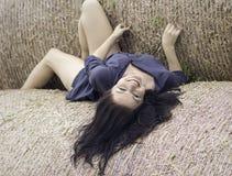 Moça em um fundo do monte de feno Fotografia de Stock