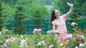 Moça em um jardim entre rosas bonitas Cheiro das rosas filme