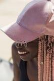 Moça em um maiô e em um tampão pretos com o pigtai cor-de-rosa longo Fotografia de Stock