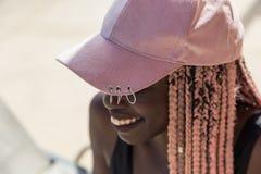 Moça em um maiô e em um tampão pretos com o pigtai cor-de-rosa longo Imagem de Stock Royalty Free