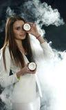A moça em um revestimento branco guarda um coco perto de seu olho e sorri em um fundo preto, coberto com o vapor do fumo Imagem de Stock Royalty Free
