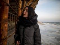 A moça em um revestimento está perto das estruturas oxidadas do metal perto da costa de mar foto de stock royalty free