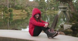 Moça em um revestimento vermelho que senta-se em uma ponte que sorri para fotos em um jardim japonês em Kanazawa, Japão vídeos de arquivo