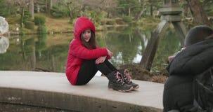Moça em um revestimento vermelho que senta-se em uma ponte que sorri para fotos em um jardim japonês em Kanazawa, Japão video estoque