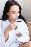 Moça em um roupão branco com xícara de café imagens de stock