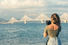 Moça em um t-shirt e em umas calças apertadas com tripé e câmera que toma a imagem da ponte de Rion-Antirion Patras Greece Imagem de Stock Royalty Free