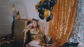 Moça em um vestido do ouro com um vidro de martini filme