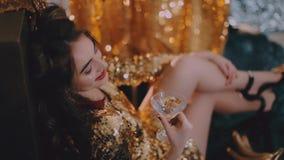 Moça em um vestido do ouro com um vidro de martini vídeos de arquivo