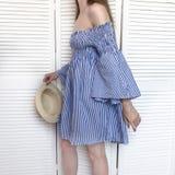 Moça em um vestido listrado no fundo de uns seixos brancos fotografia de stock royalty free