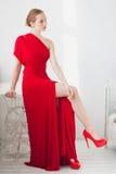 Moça em um vestido vermelho em um fundo branco imagem de stock royalty free