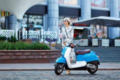 Moça em uma bicicleta motorizada na cidade imagens de stock