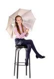 A moça em uma cadeira com um guarda-chuva imagem de stock