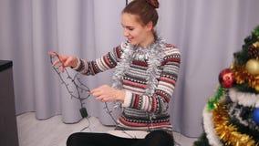 A moça em uma camiseta feita malha decora uma árvore de Natal, tentando desenrolar uma festão e resolvendo um problema cheerful vídeos de arquivo
