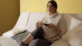 Moça em uma camiseta morna acolhedor no inverno que nivela em casa o chá bebendo e que olha a tevê video estoque