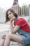 A moça em uma camiseta vermelha de lãs e no short das calças de brim está sentando-se nas etapas Fotografia de Stock