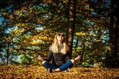 Moça em uma grinalda das folhas A menina no parque outono foto de stock