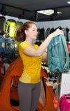 A moça em uma loja de especialidade para o turismo escolhe a trouxa Imagem de Stock