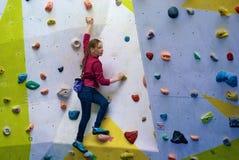 Moça em uma parede de escalada Fotos de Stock Royalty Free