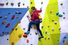 Moça em uma parede de escalada colorida Imagem de Stock Royalty Free