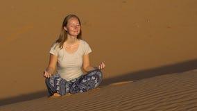 A moça em uma pose dos lótus encontra o alvorecer no deserto vermelho filme