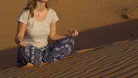 A moça em uma pose dos lótus encontra o alvorecer no deserto vermelho vídeos de arquivo