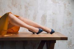 Moça em uma saia amarela e em umas sapatas azuis no interior imagens de stock