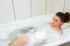 A moça encontra-se na água quente no banho com espuma fotos de stock