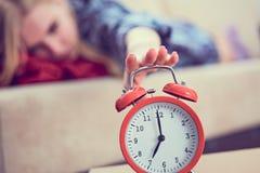 A moça encontra-se no sofá e estica-se sua mão ao despertador vermelho para desligá-lo Acorde tarde imagens de stock royalty free