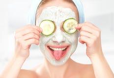 Moça engraçada com uma máscara para a cara e os pepinos da pele fotografia de stock