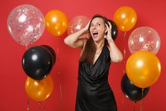Moça entusiasmado em pouco vestido preto que comemora aderir-se a dirigir em balões de ar vermelhos brilhantes do fundo ` S do Va imagens de stock